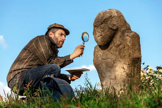 Scientist historian examines  stone sculpture on  mound through magnifying glass
