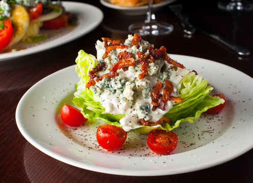 Wedge Salad. Iceberg Lettuce, blue cheese dress and shredded carrots. Classic American steakhouse or restaurant favorite.