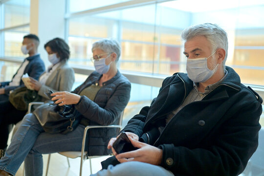 Patients sitting in waiting room with face mask, COVID-19 pandemic
