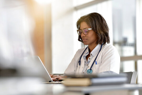 Woman doctor working in office with laptop computer