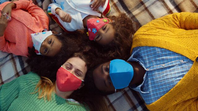 Top view of happy diverse family in safety mask relaxing on blanket during picnic