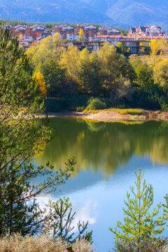 Bansko, Bulgaria autumn panorama background of Pirin mountain peaks, lake water, colorful green, red and yellow trees reflection