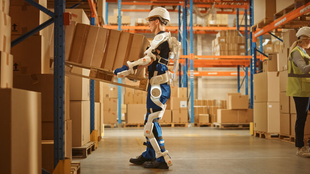 High-Tech Futuristic Warehouse: Worker Wearing Advanced Full Body Powered exoskeleton, Lifts Heavy Pallet full of Cardboard Boxes. Delivery Exosuit amplifies strength.