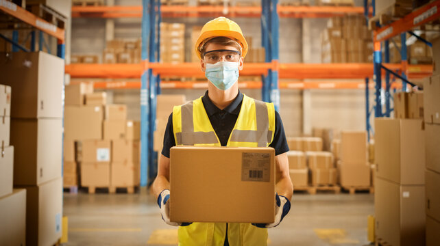Portrait of Handsome Male Worker Wearing Medical Face Mask and Hard Hat Holds Cardboard Box While Standing in Big Retail Warehouse full of Shelves with Goods. Safety First Protective Workplace