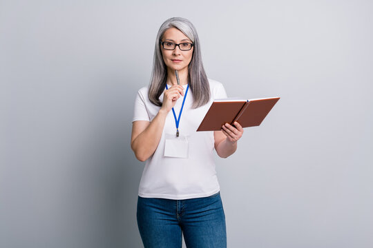 Photo of attentive senior lady wear casual outfit eyeglasses pen chin holding copybook isolated grey color background