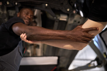 focus on hands of diverse men holding each other, in auto service repair shop, help Wall mural