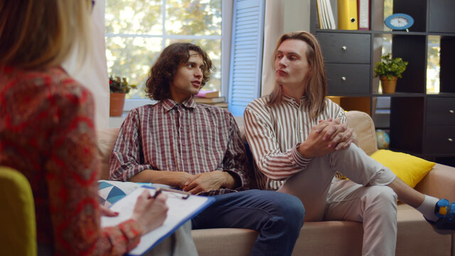 Unhappy gay couple sitting on sofa and talking to psychologist