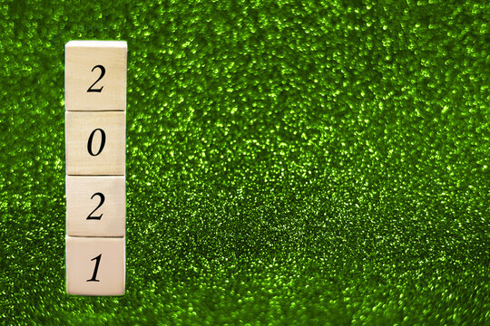 Wooden cubes with numbers 2021 on green sparkling background.
