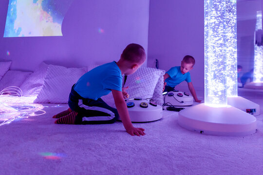 Child with intellectual disability in sensory stimulating room, snoezelen. Autistic child interacting during therapy session.