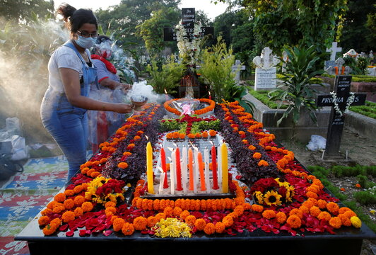 Women burn incense as they pray by the grave of their relative during All Souls Day in Kolkata