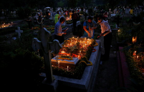 People light candles and lay flowers on the graves of their relatives at a cemetery during All Souls Day