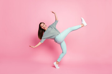 Full size photo of crazy funky young woman dancing wear shirt blue pants white sneakers isolated on...