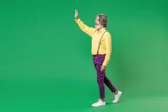 Full length side view of funny elderly gray-haired mustache bearded man in yellow shirt suspenders waving and greeting with hand as notices someone isolated on green colour background studio portrait.