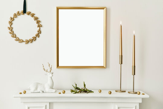 Christmas composition with gold mock up poster frame, white chimney and decoration. Christmas trees and wreath, candles, stars, light and elegant accessories. Template.