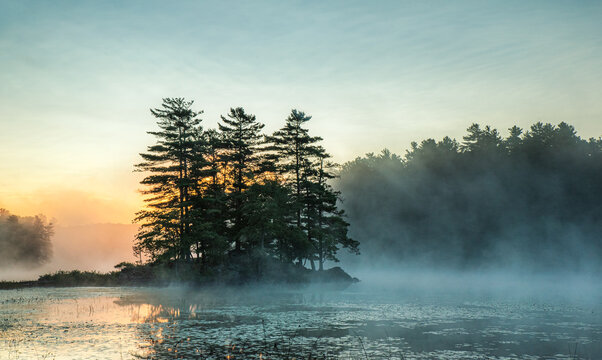 Mist rising off of a lake in the morning in Ontario, Canada.