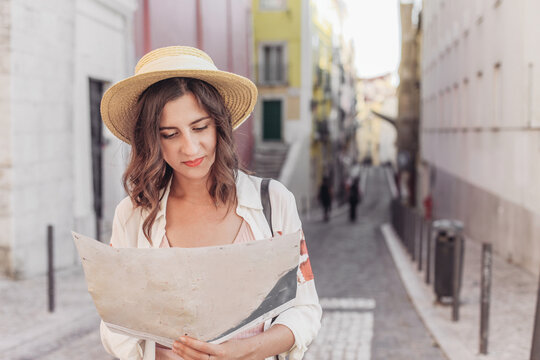 Young woman in hat looking at a map on a small street of European town