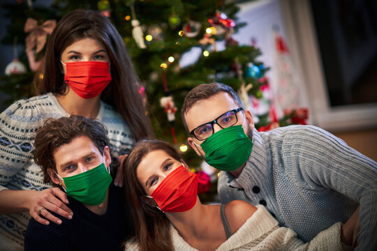 Group of friends wearing masks exchanging Christmas presents at home