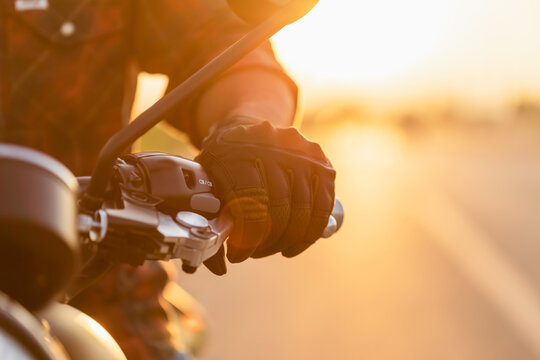 Macro left hand of motorcyclist wearing riding glove on the clutch. Outdoor shooting on the road with copy space