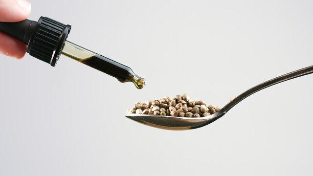 CBD Hemp oil in a pipette and cannabis seeds on spoon. Alternative medicine concept.