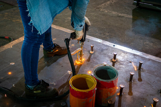 A welder is using a Stud Welding Machine to weld stud bolt on steel plate, at industrial factory.
