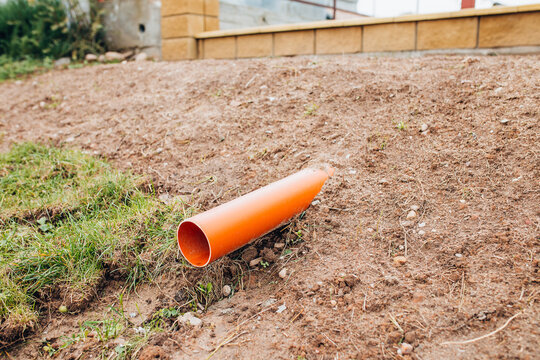 Conclusion of a plastic storm pipe from under the ground - drainage of rainwater into the storm sewer