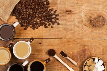 Cafe solo y café con leche sjunto a granos de café, un cuenco con azúcar y cucharas sobre una mesa de madera rústica. Vista superior. Copy space