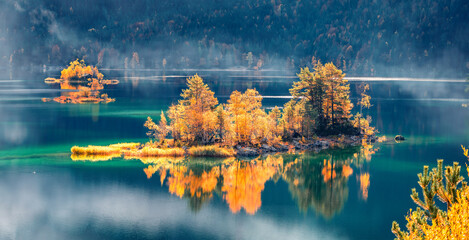 Panoramic morning view of Eibsee lake. Picturesque autumn scene of Bavarian Alps, Germany. Colorful mountain hills reflected in the calm surface of water ot pure lake.