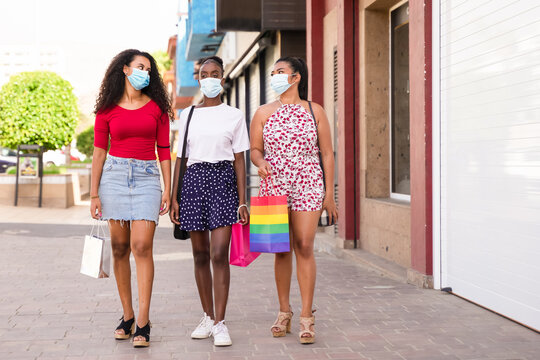 Friendship shopping with protective masks for coronavirus. A picture of girls with shop bags, closed shops. Shopping, tourism and virus concept.
