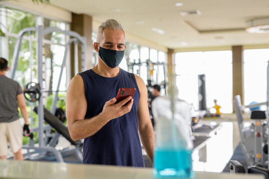 Mature Persian man with mask registering with phone for entrance at the gym