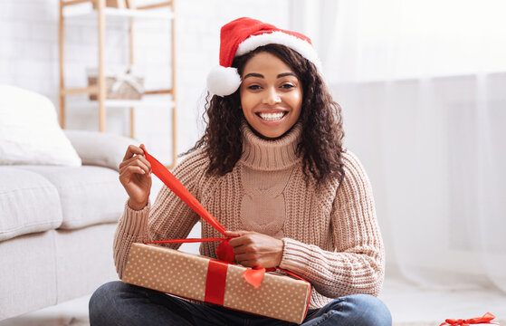 Black Woman Opening Gift Box At Home
