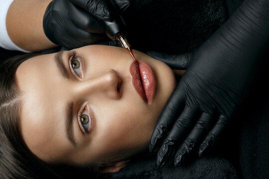 Gorgeous brunette woman having lip permanent