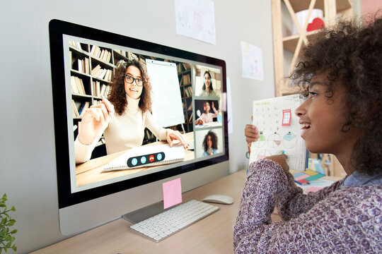 Cute african kid child girl showing homework talking to remote teacher distance learning during virtual online class on video conference call with tutor and school children group at home on computer.