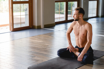 30-35s male yogi sitting peacefully in lotus inside spacious studio with big windows