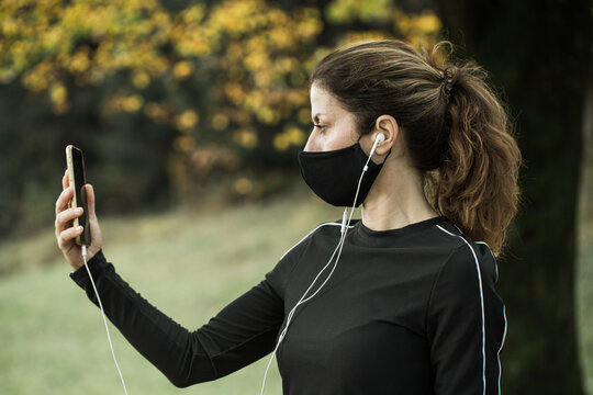 Woman with face mask taking video call. Giving lectures while working out during covid-19.
