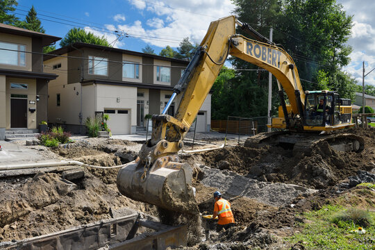 Worker tamping earth and aggregate in trench for new sewer installation with help of excavator on residential street Nepean, Canada - July 23, 2020
