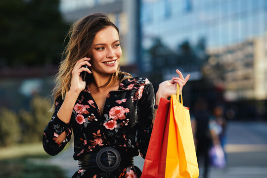 Happy young woman holding shopping bags and talking on the phone on the street