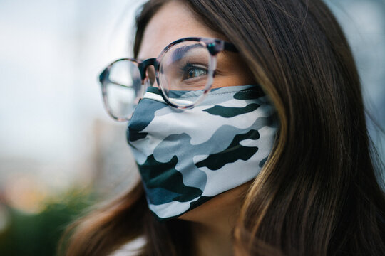Close up of young woman with glasses wearing camo mask