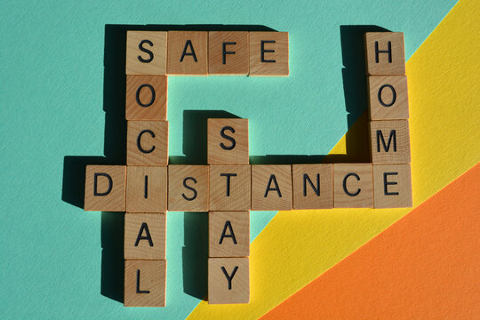 Social, Distance, Stay, Safe, Home, words in crossword form  in wooden alphabet letters isolated on colorful background