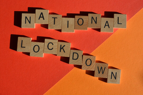 National lockdown, words in wooden alphabet letters on red and orange background