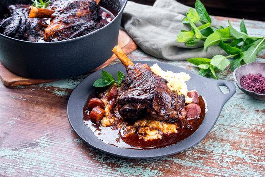 Modern Style traditionelle geschmorte Lammhaxen in Rotwein Sauce mit Schalotten und Kartoffel Püree angeboten als close-up auf einem Design Teller