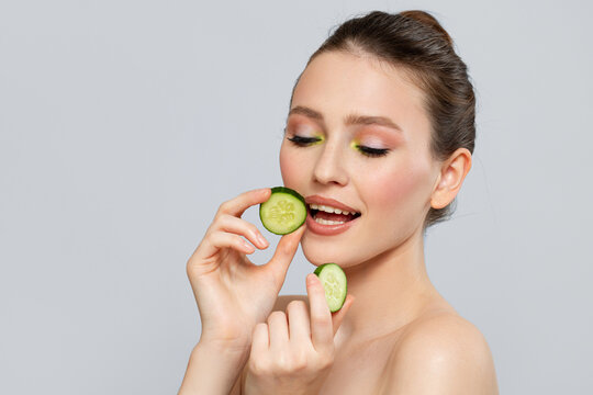 Beautiful young smile woman holding fresh cucumber slices. Skin care, spa, natural beauty and cosmetology concept, on gray copyspace background