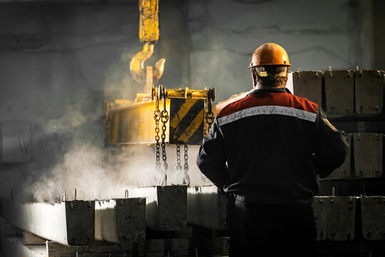 A male worker controls the production process in a factory as a crane moves a reinforced concrete product with holes. Reinforced concrete pillars secured with metal hooks and chains