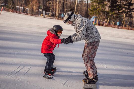Dad teaches son snowboarding. Activities for children in winter. Children's winter sport. Lifestyle