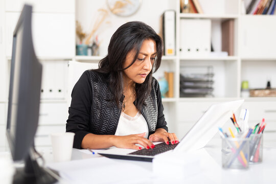 Portrait of busy female entrepreneur sitting at office desk with papers and laptop ..