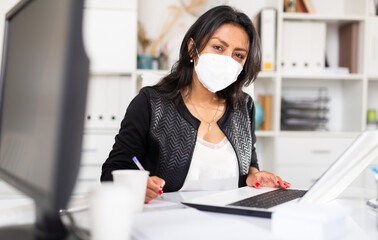 Portrait of confident Latina wearing medical mask working on laptop in office. New life reality...