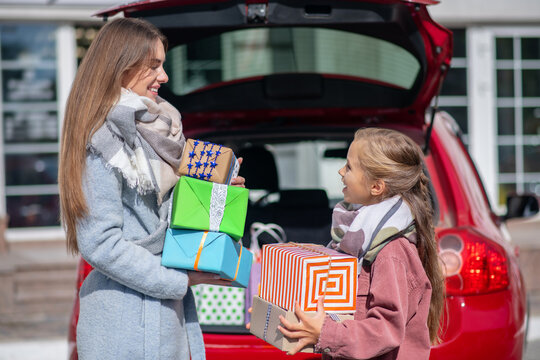 Mom and daughter looking at each other, standing with gift boxes at car trunk
