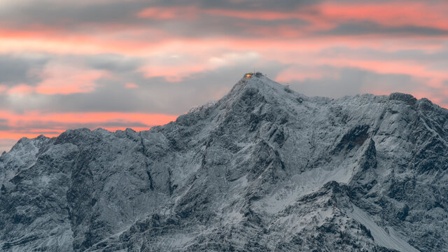 Sunrise at mountain zugspitze in winter with snow and colorful sky. Highest german mountain. Cable car. Germany austria