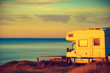 Camper vehicle on beach at sunrise