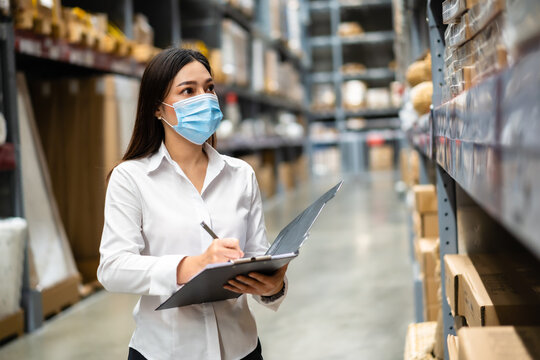woman worker with medical mask holding clipboard and checking inventory in warehouse during coronavirus (covid-19) pandemic