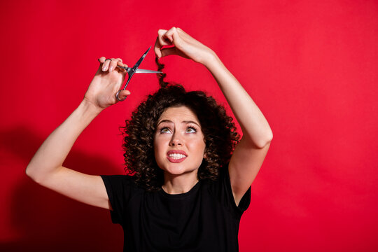 Photo of unsatisfied person cutting hair hand hold scissors bad decision isolated on bright red color background